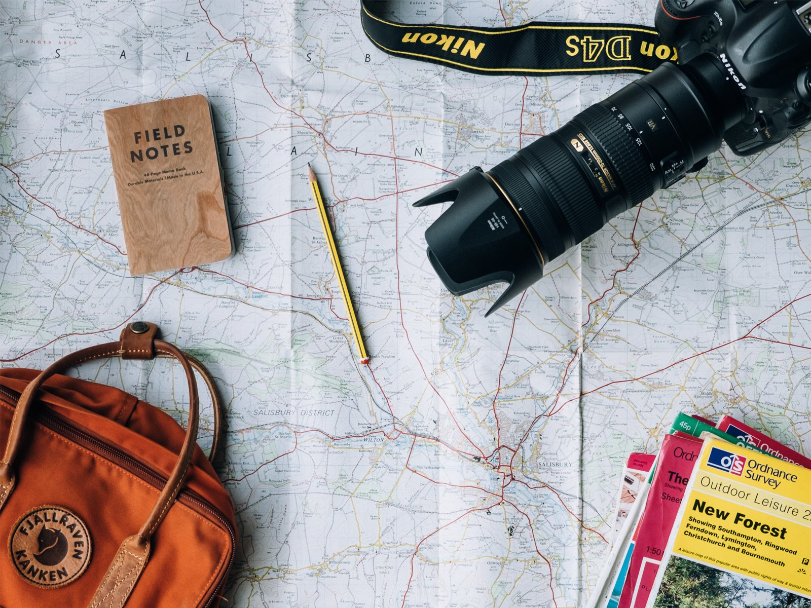 camera, travel books, and backpack laid out on a map