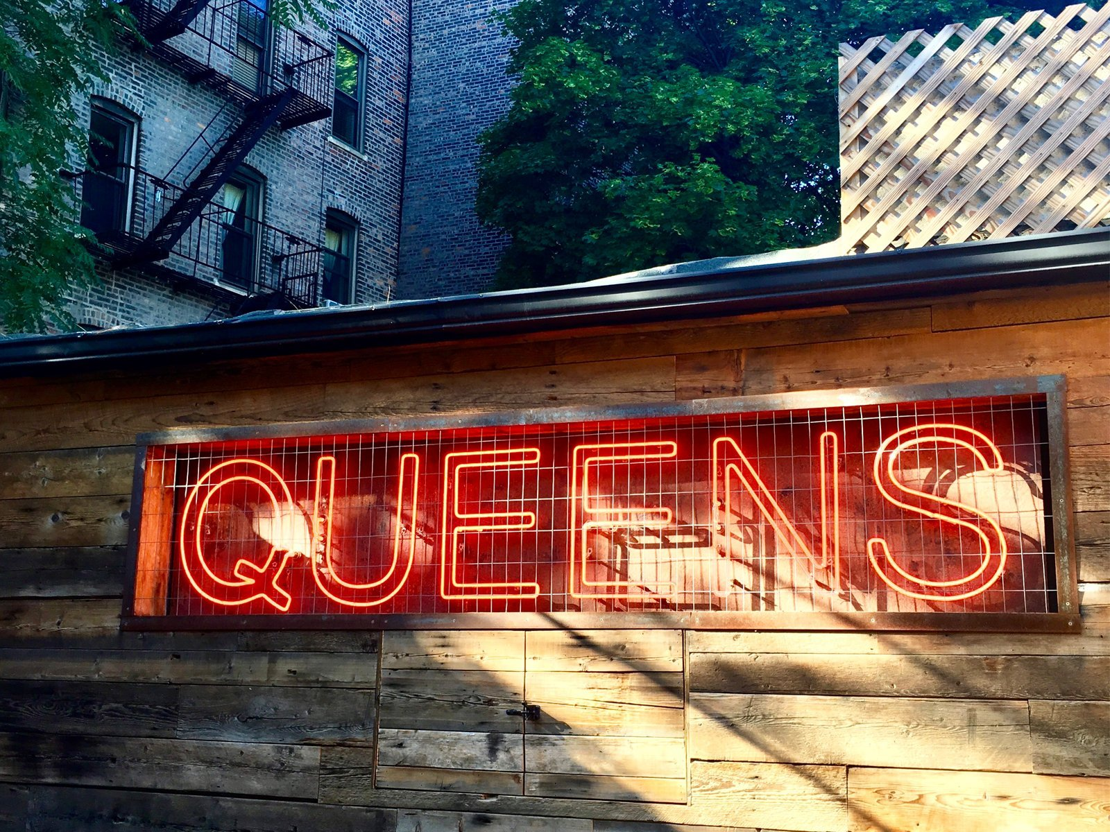 "A neon sign that reads ""Queens"" at Sek'n Sun in Astoria, Queens"