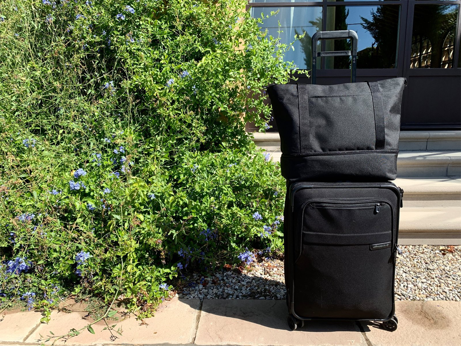 a suitcase and duffel bag are two of my travel essentials