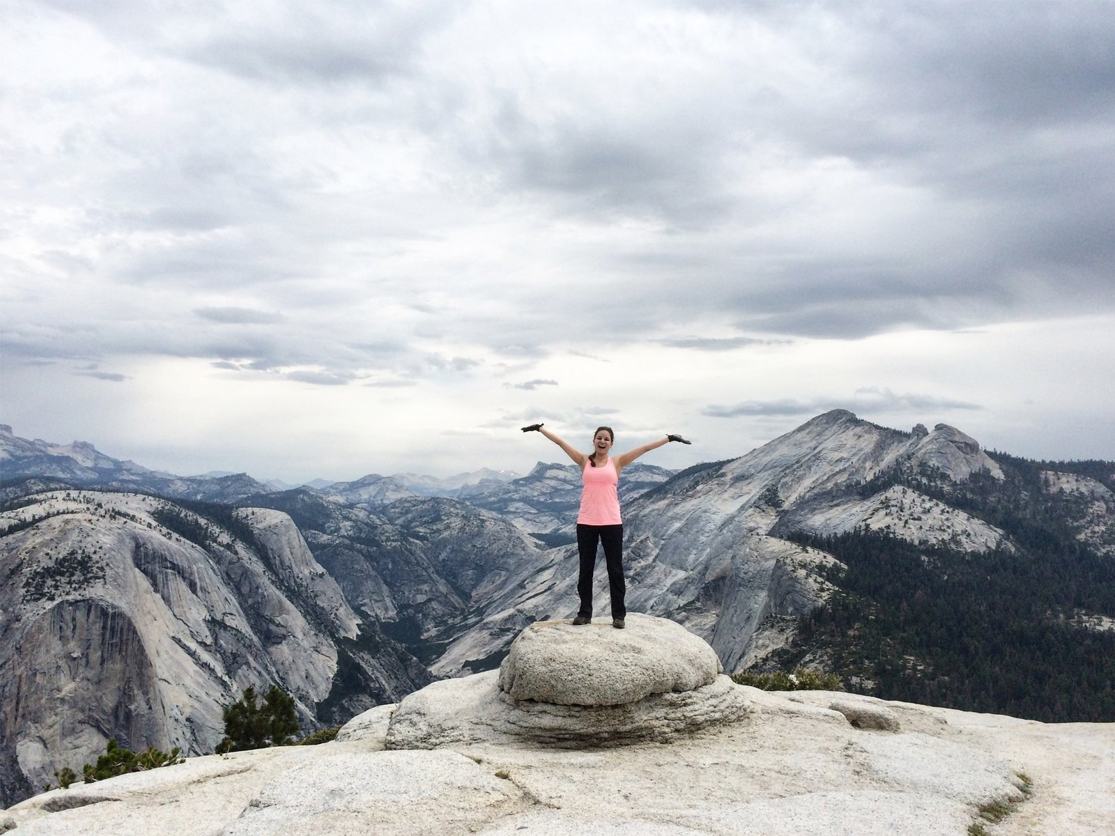 a hiker at the summit of half dome in yosemite national park