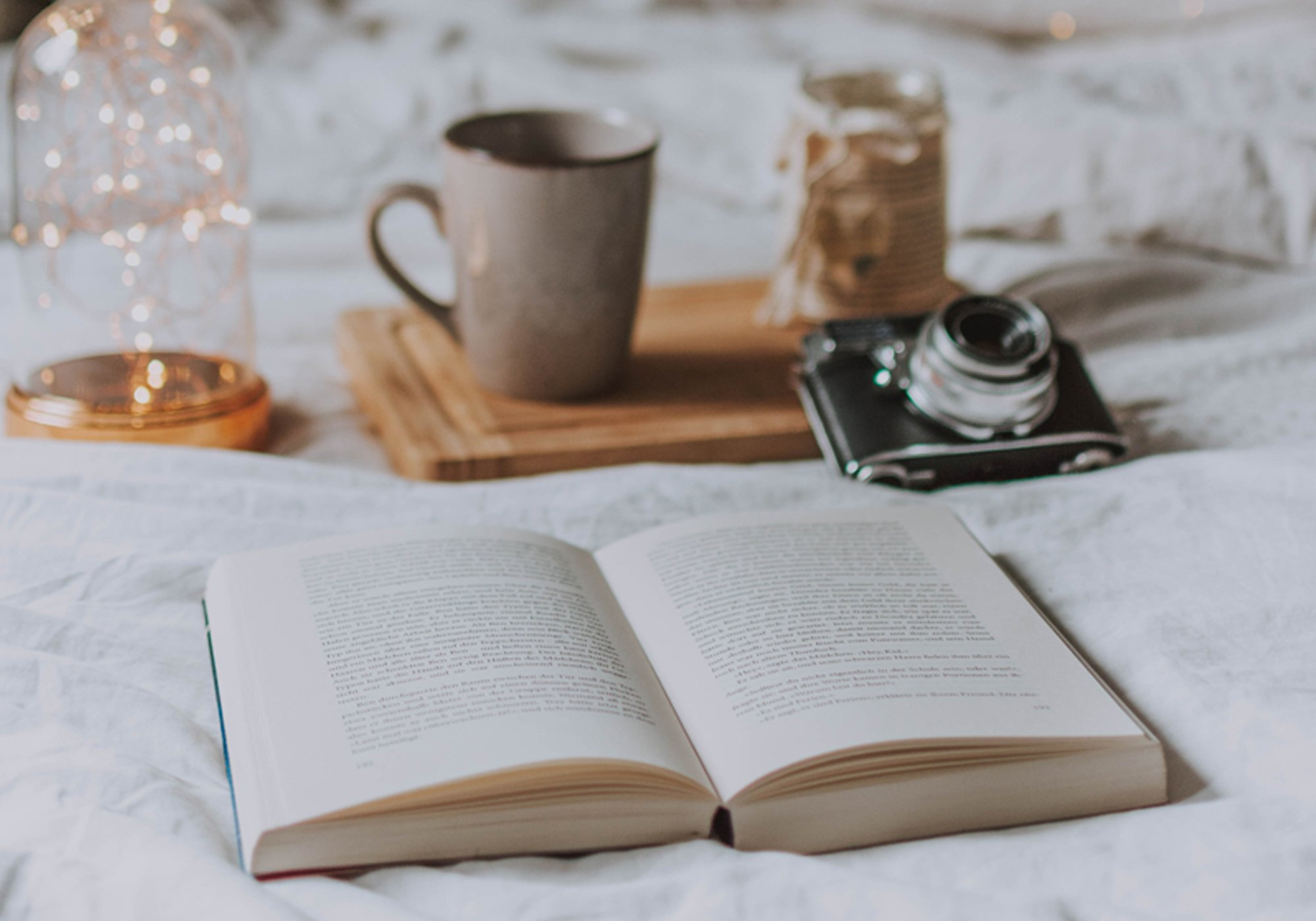 a book, a camera and a cup of coffee on a bed