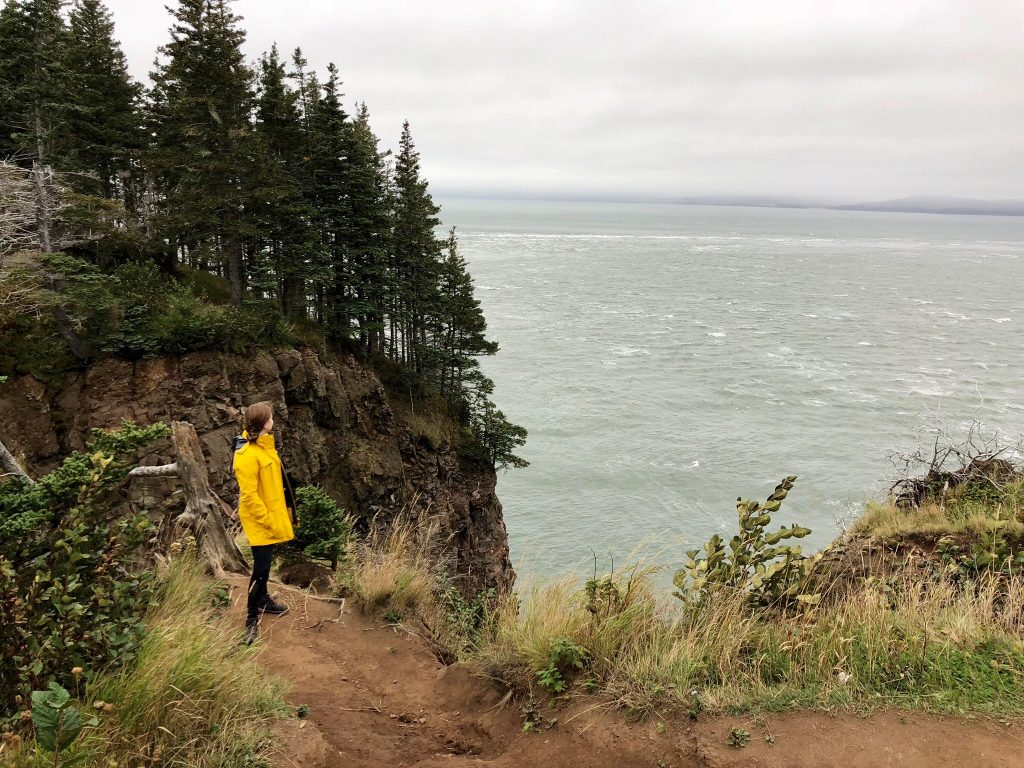 a woman hiking Cape Split overlooking the Bay of Fundy in Nova Scotia