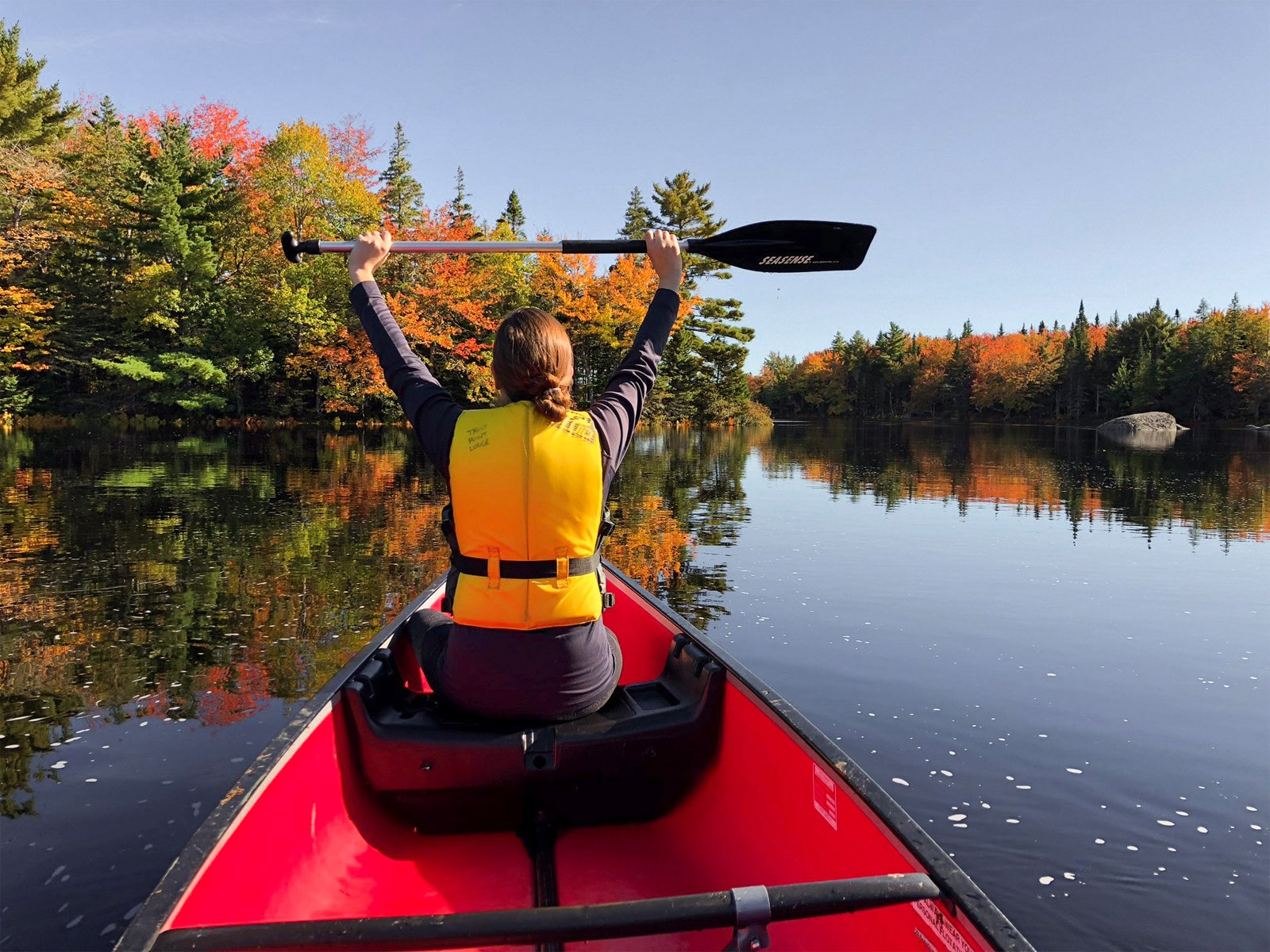 a woman canoeing in the fall on the Tasket River at Trout Point Lodge, Nova Scotia
