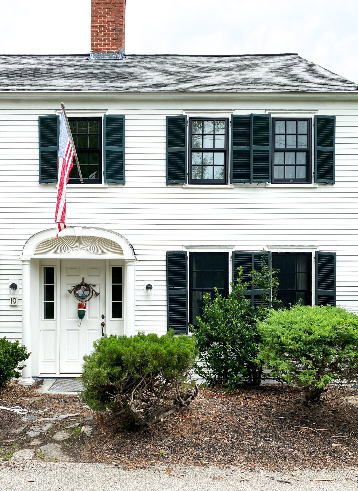 a nautical white house with black shutters in New Castle, NH