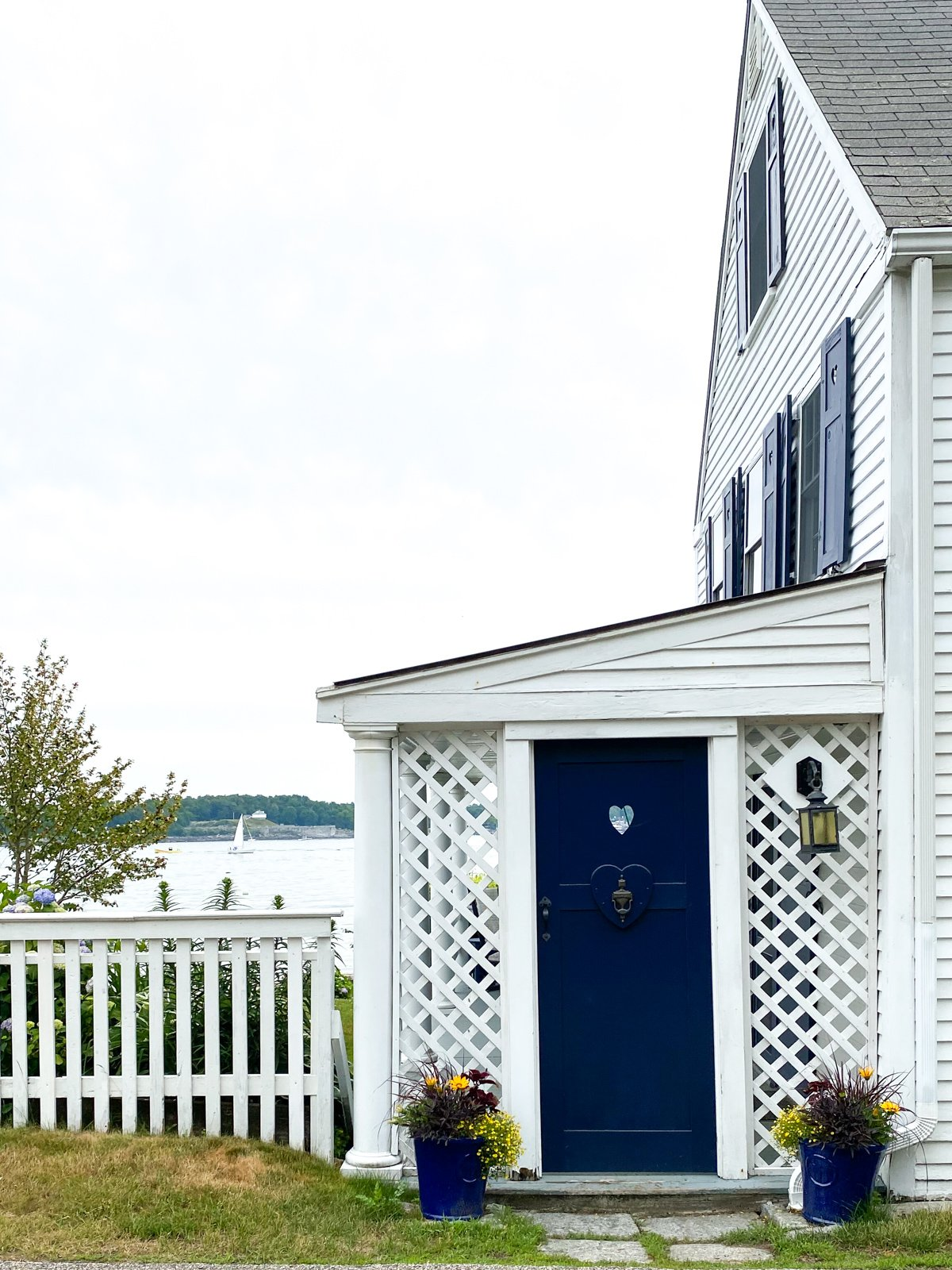 a blue door and white picket fence in New Castle, NH