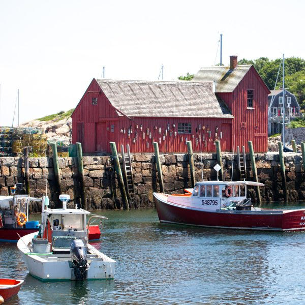 a red building and boats in the harbor in Rockport, MA