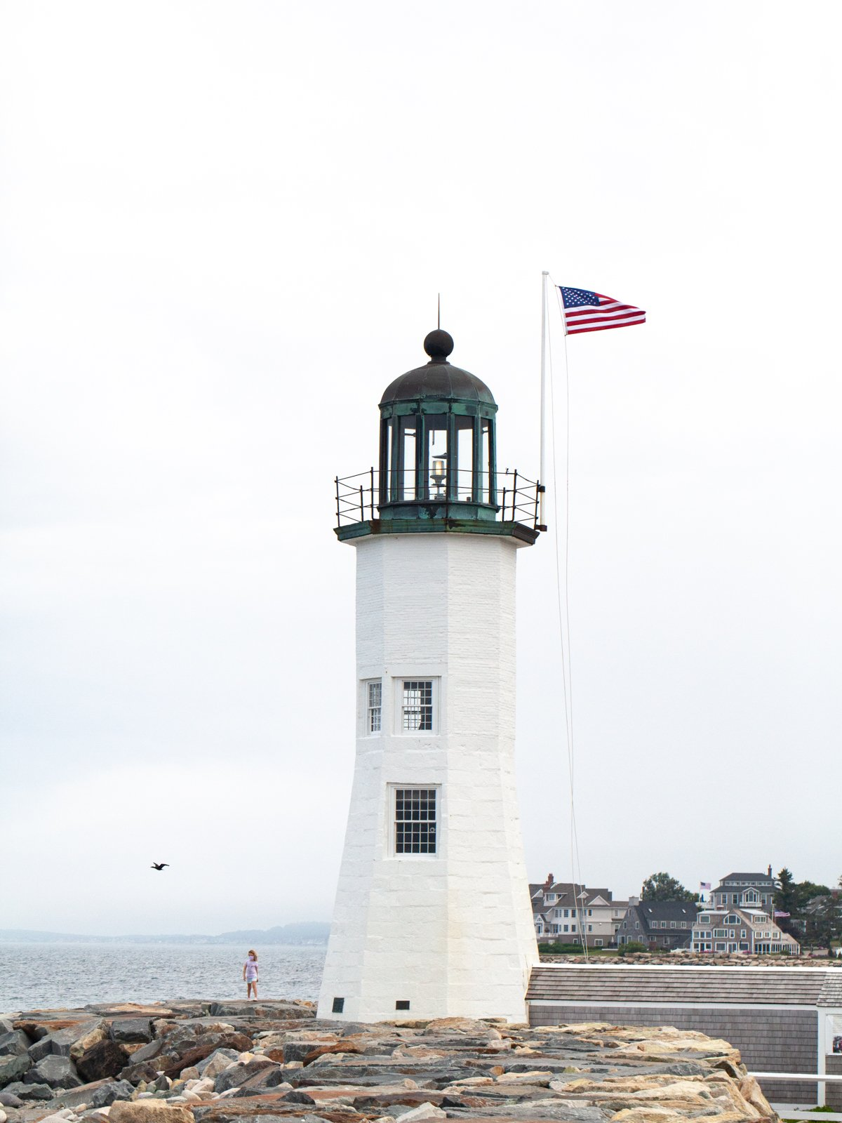 a white lighthouse with an american flag in scituate, massachusetts
