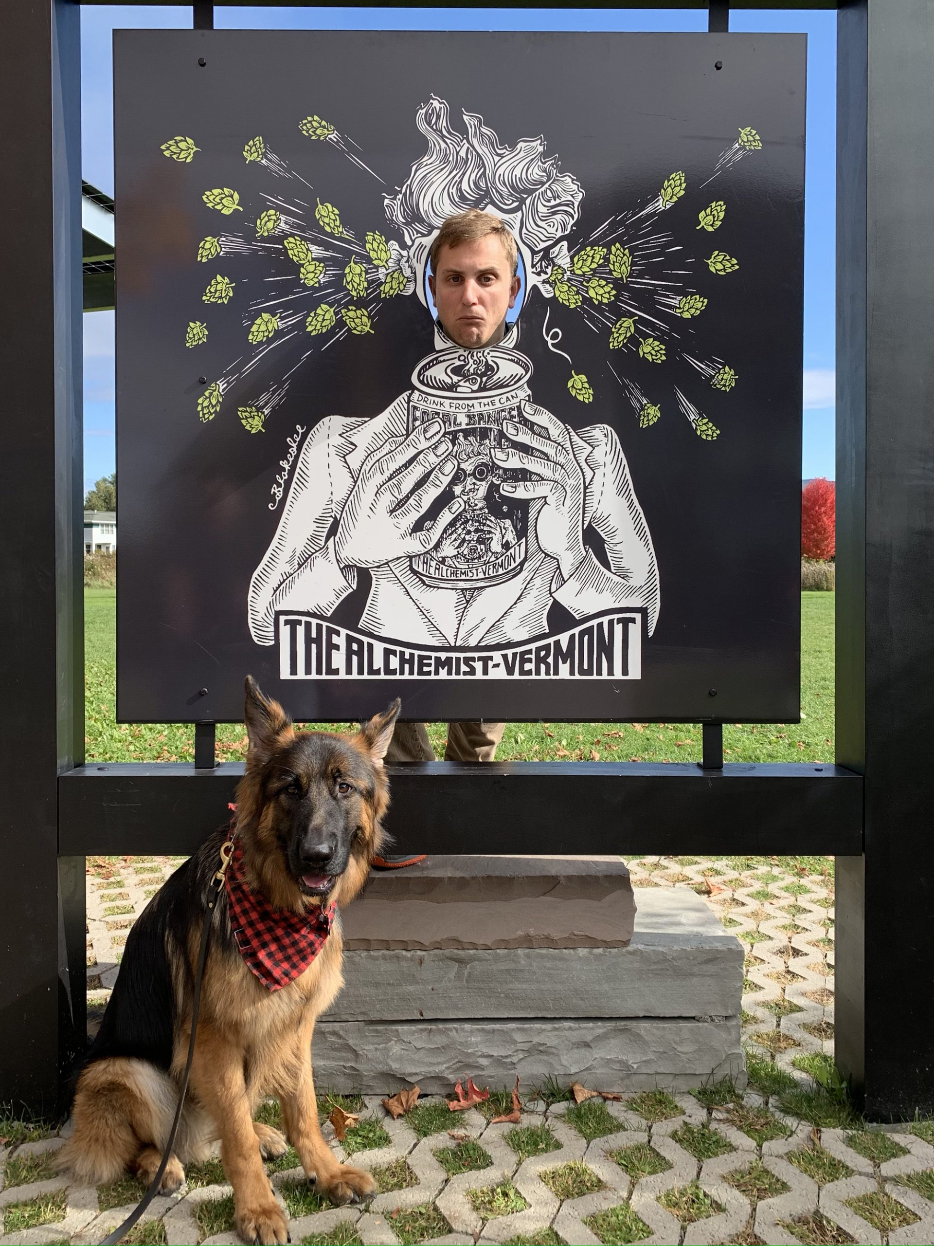 a dog sitting in front of a sign that reads The Alchemist Vermont