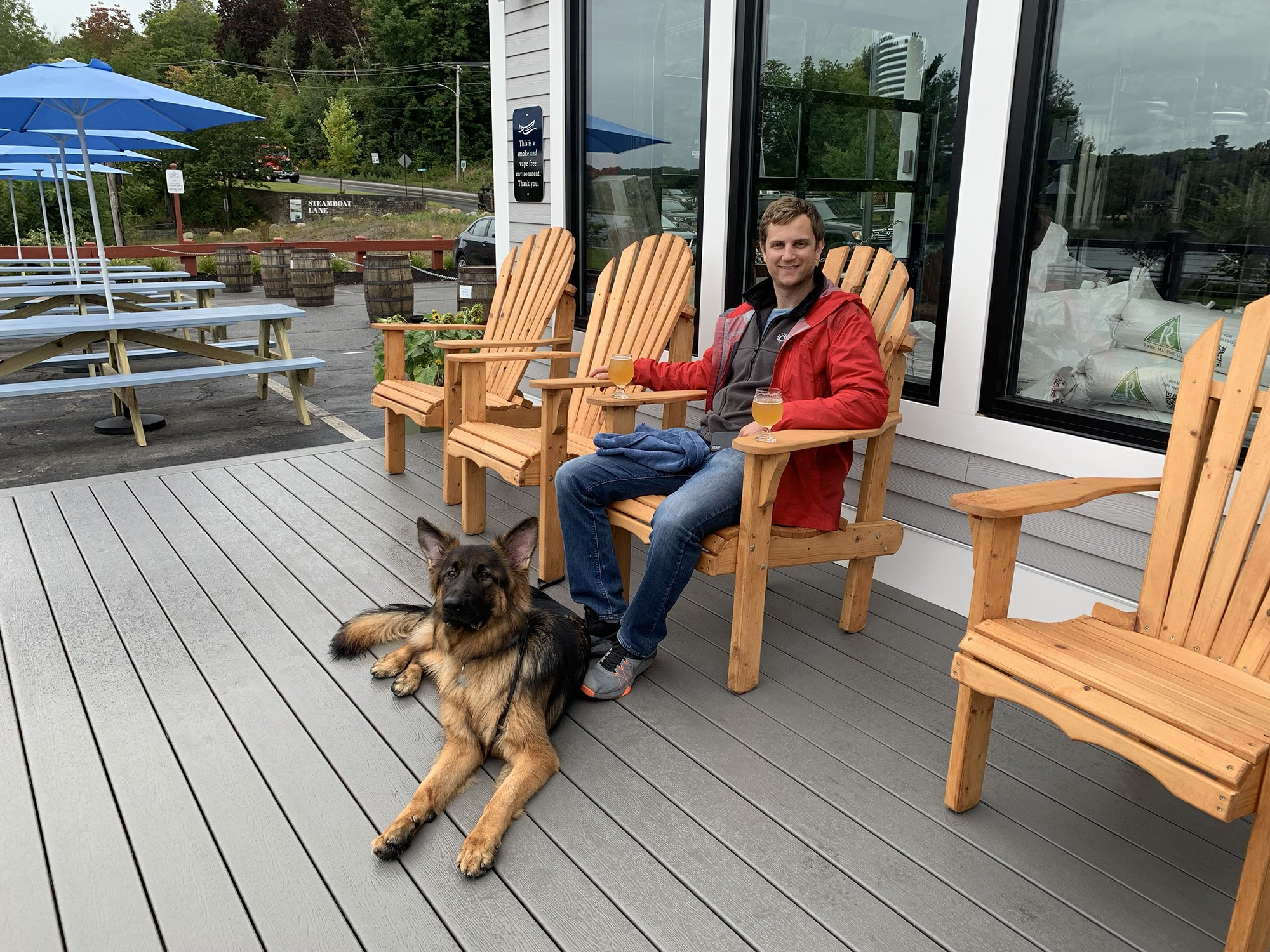 a man and his dog sitting in an Adirondack chair on the deck enjoying a glass of beer at Bateau Brewing in Gardiner, Maine.