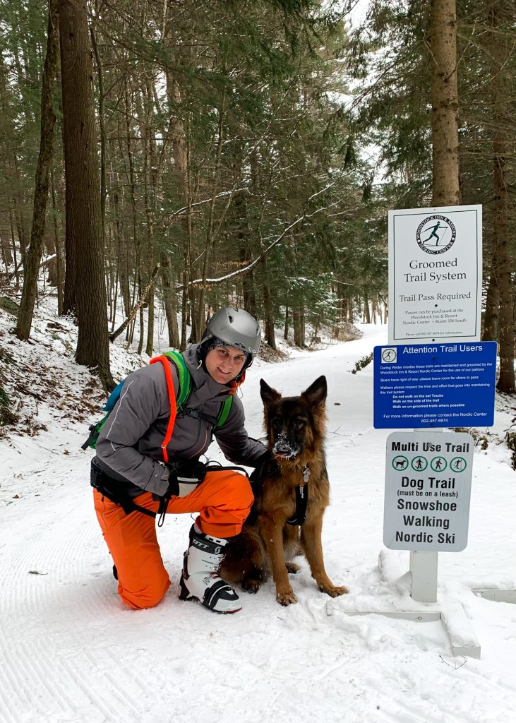 a skiier and a dog at the start of the dog friendly trails at Woodstock Inn and Resort Nordic Center in Vermont