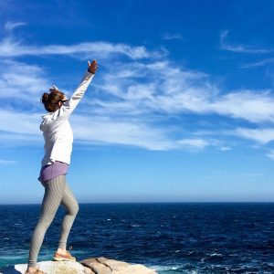 woman standing on the cliffs by the ocean at Peggy's Cove near Halifax, Nova Scotia